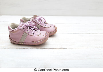 Pink little boots for a girl on a white wooden background