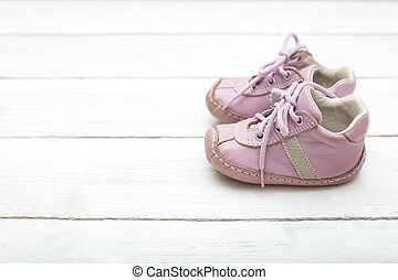 Pink little shoes for a girl on a white wooden background
