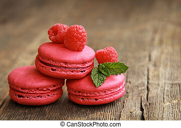 Three raspberry macarons on a wooden table with fresh fruits and mint