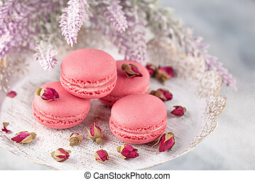 Pink macaroons on a vintage plate and dried flower buds. Pastel colored.