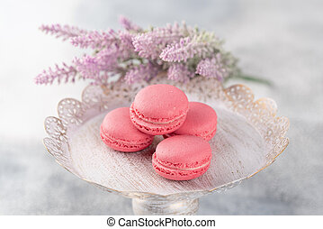 Pink macaroons on a vintage plate and flowers. Pastel colored.