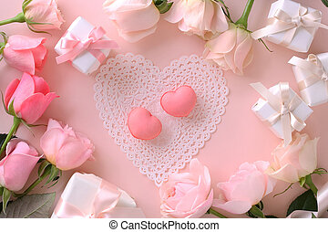 Pink macaroons with beautiful pink tone roses and gift boxes on pastel pink background, top view