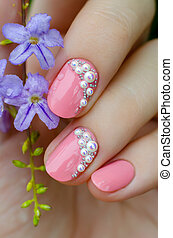 Pink manicure with mini pearls and small purple flower
