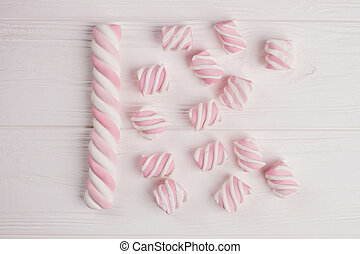 Pink marshmallow on wooden background.