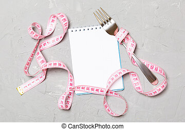 Pink measure tape, open notebook and fork on cement background with empty space for your idea. Top view of healthy lifestyle concept