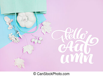 Pink mockup with pumpkin, berries, leaves and package on a multicolor pastel autumn background. Greeting card for Thanksgiving Day in rustic style with text Hello Autumn. Flat lay. Top view