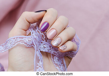 Pink nail art with glitter accent. Beautiful female hand...