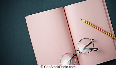Pink notebook on two-tone gray background top view