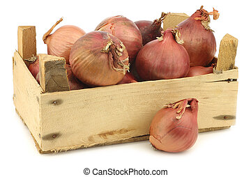 pink onions in a wooden crate