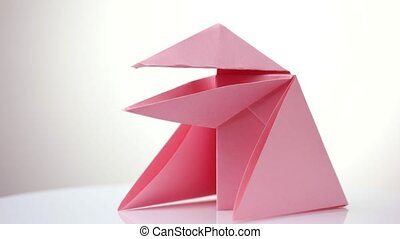 Pink origami snapper. White isolated background.