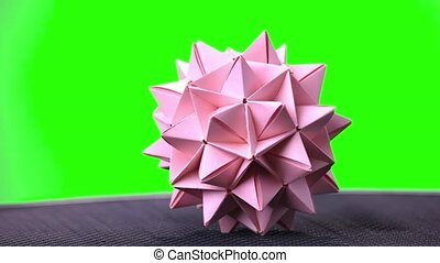Pink origami spiky ball. Green hromakey background for...