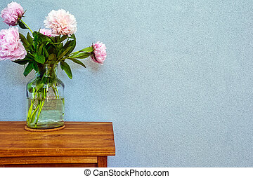 Pink peonies in glass vase on wooden table, romantic design with space for text modern interior