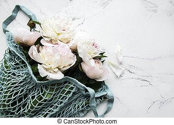 Pink peony flowers in string bag