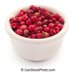 Pink peppercorn in ceramic bowl over white background