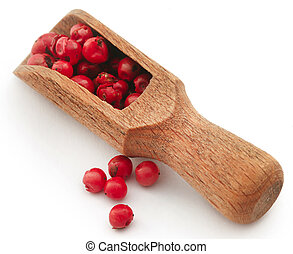 Pink peppercorn in wooden spoon over white background