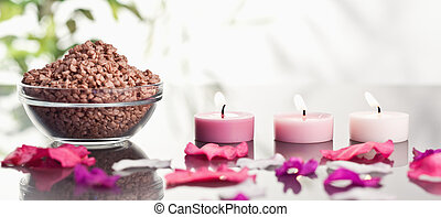 Pink petals with lighted candles and a bowl of brown gravel