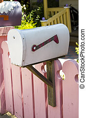 pink picket fence with white vintage mailbox