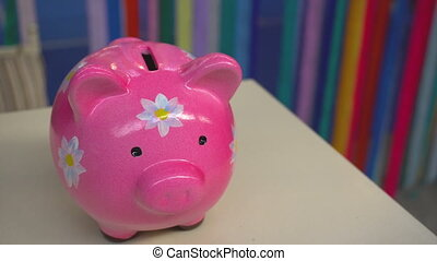 Pink pig moneybox with flowers standing on desk. View from...