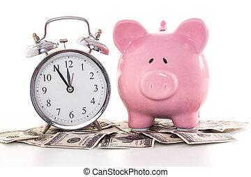 Pink piggy bank beside alarm clock on dollars on white...