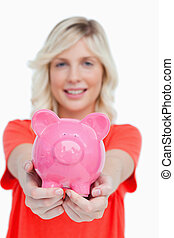 Pink piggy bank held by a smiling attractive woman