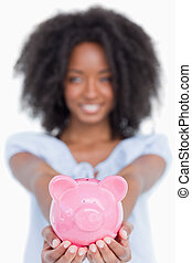 Pink piggy bank held by a young smiling woman with curly hair