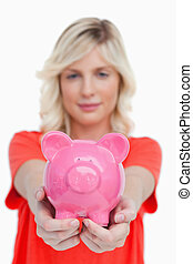 Pink piggy bank held by a young woman