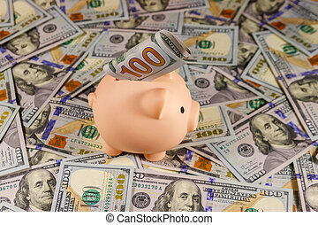 Pink piggy bank on a background of american one hundred dollars bills