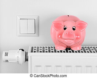 Pink piggy bank saving electricity and heating costs, close...