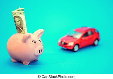 Pink piggy bank with a car on the table. Tinted. Concept of saving finances and contributions to property.