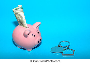 Pink piggy bank with a house on the table. Tinted. Concept of saving finances and real estate deposits.
