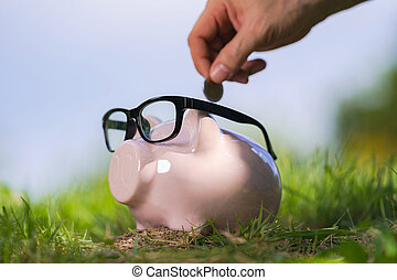 Pink piggy bank with glasses on grass and hand putting in a coin