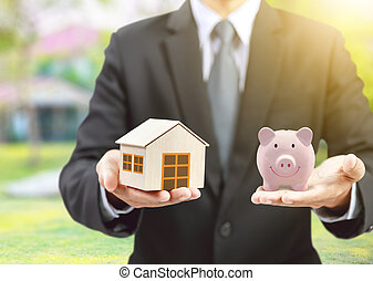 pink piggy ceramic bank and home model with businessman, insurance concept