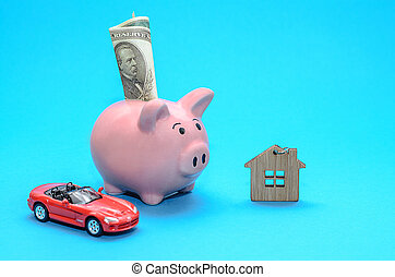 Pink piggy piggy bank with a house and a car on the table. Tinted. Concept of saving finances and real estate deposits.