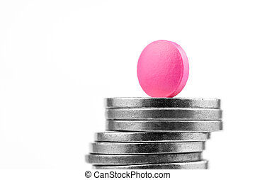 Pink pill on a stack of coins on a white background. Success in the drug business.