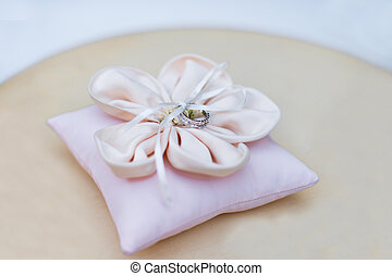 Pink pillow with wedding rings on the table
