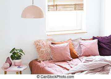 Pink pillows on bed next to table with plant in bright bedroom interior with window and lamp. Real photo