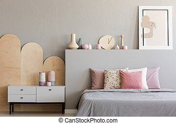 Pink pillows on grey bed in modern bedroom interior with poster and cabinet. Real photo