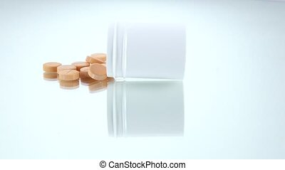 Pink pills in a bottle, on white, rotation, reflection