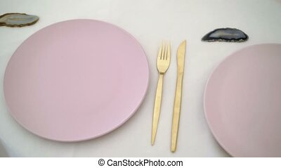 Pink plates and golden knife and fork on table