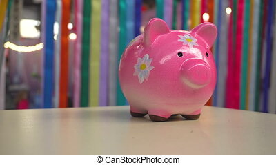 Pink porcelain pig moneybox with flowers standing on desk....