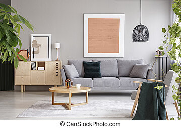 Pink poster above grey sofa in living room interior with wooden table near cupboard. Real photo