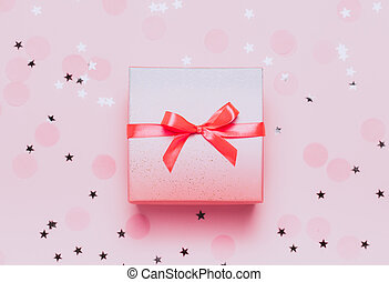 Pink present box on pink konfetti background. Top view, flat...
