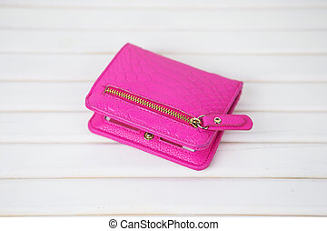 pink purse on a white wooden background, top view