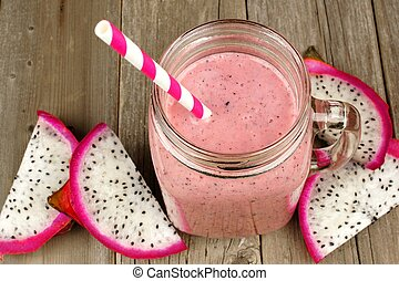 Pink raspberry, dragon fruit smoothie in jar mug on a wood background