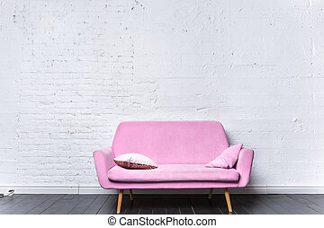 Pink retro sofa against white brick wall
