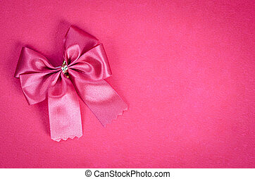 Pink ribbon on pink background.