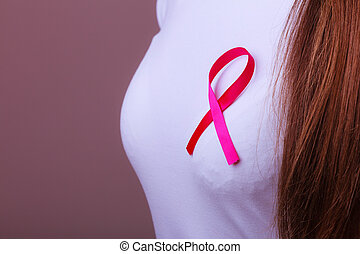 Pink ribbon on woman chest to support breast cancer cause