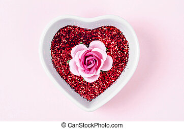 Pink rose and red glitter in white heart shaped bowl.
