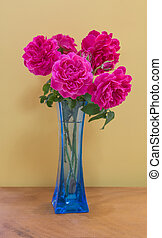 Pink rose bouquet in blue vase over yellow wall on plank wooden table
