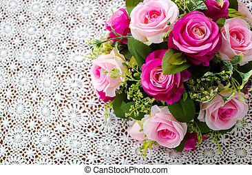 pink rose bouquet on white crochet tablecloth